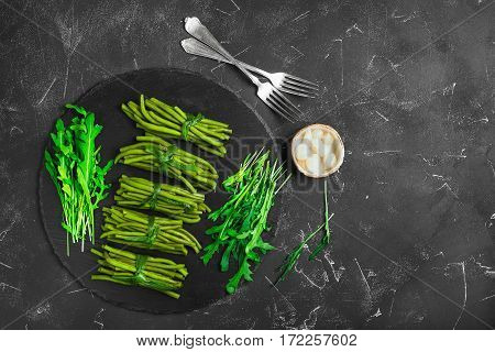Cooked boiled stewed green beans tied in bundles of green onions. Ingredients for the green beans pickled onions and fresh arugula. Black concrete background. Top view from above and copy space.