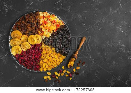 Assortment of dried fruit and candied fruit. Fruits figs prunes raisins papaya pineapple cranberries are laid out in rows on black background in the glass dish. Dry fruits in measuring spoon.