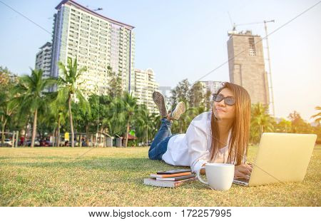 Women work in the park with the laptop and coffee relax work background city