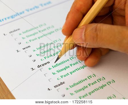 multiple choice english exam on table with hand