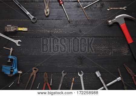 Old working tools on a dark black wood background