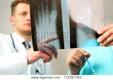 healthcare medical and radiology concept - Male doctors looking at x-ray of foot