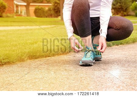 young woman runner tying shoelaces outside. House background outside.