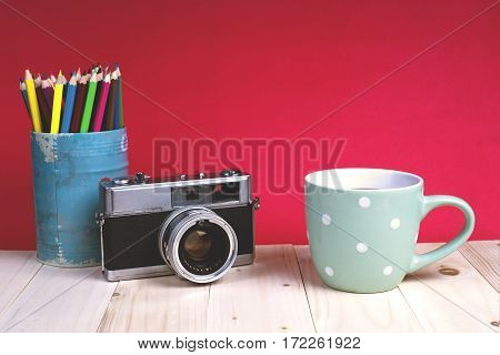 coffee cup with old camera on wall paper red background