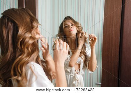 Young Cute housewife looking in the mirror. Girl in sexy lingerie robe and preens. Good morning. Morning makeup