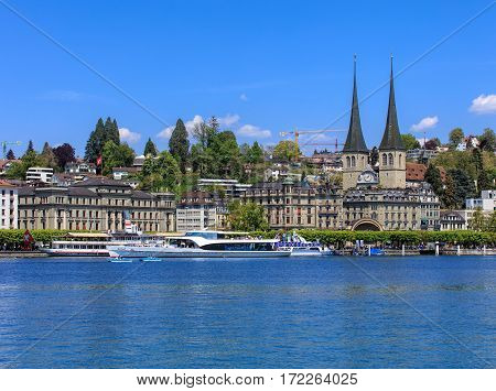 Lucerne, Switzerland - 8 May, 2016: people in boats on Lake Lucerne, buildings on National quay and towers of the Church of St. Leodegar in the background. The Church of St. Leodegar is a landmark of the city of Lucerne, Switzerland.