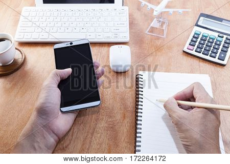 man writing notebook with pencil and use smartphone on office desk wood table of business workplace and business objects