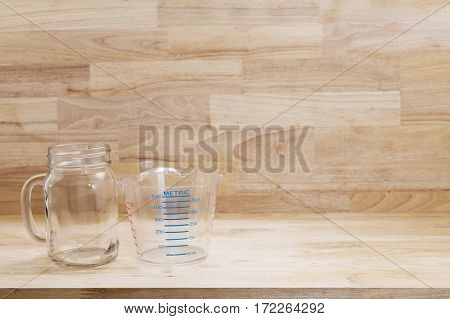 glass bottle and empty measuring cup on wooden background