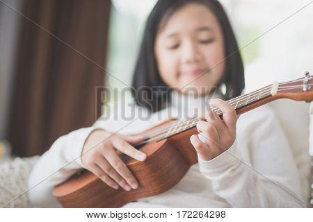 Close up Asian child playing ukulele in room