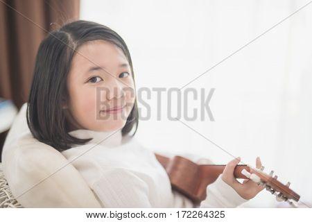 Beautiful Asian girl playing ukulele at her room
