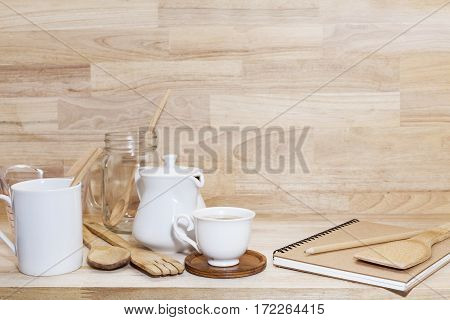 Coffee cup with glass bottle and empty measuring cupwooden spoon on wood background
