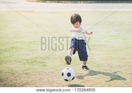 Asian boy kicking football on the field