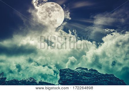 Boulder with sky background and beautiful full moon behind cloud at night. Outdoor at nighttime. Beauty of nature use as background. Cross process style. The moon were NOT furnished by NASA.