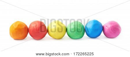 Multiple colorful plasticine balls arranged in a line, composition isolated over the white background