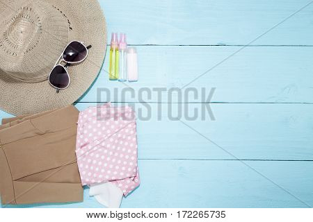 Outfit of clothes and woman accessories on blue wooden backgroundessential vacation items for travel and summer travel background