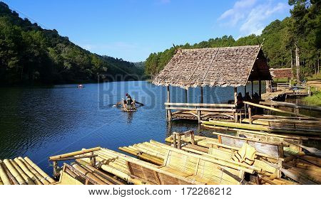 Tourists sitting on the bamboo rafts floating in Pang Oung Lake (Pang Tong reservoir) during golden sunrise morning Mae hong son Thailand.