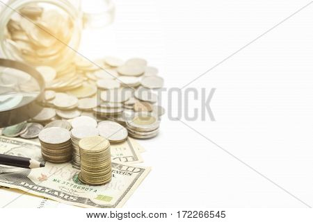 stacks of coins and dollar banknote on white background