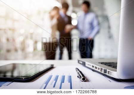 Close-up of business document in touchpad lying on the desk office workers interacting in the background.