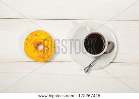 Pink donut and black coffee with copy space. Cup of black coffee with donut on a plate on white wooden table, top view, flat lay. Delicious breakfast, sweet donut and coffe.