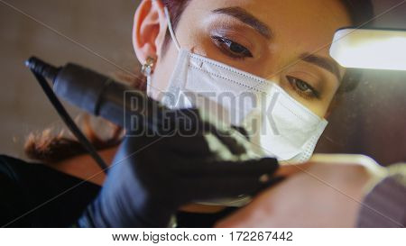 Portrait of manicure master in medical mask - Polishing nails in beauty salon, close up