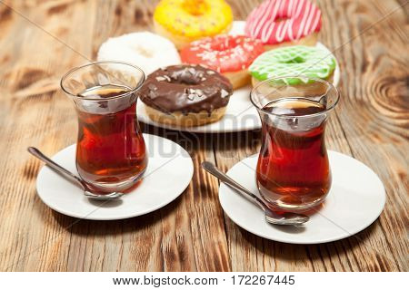 Colorful donuts and two cups of tea on a wooden table