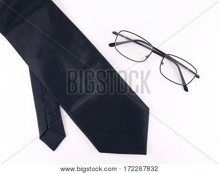black simple necktie with eyeglasses isolated on white background, clothes accessory for men in formal style