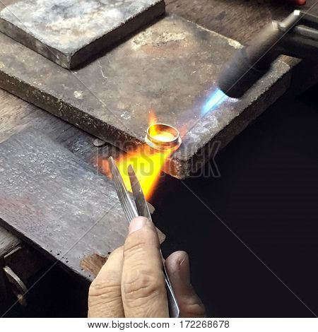 A gold making worker is firing on the gold ring to adjust its shape
