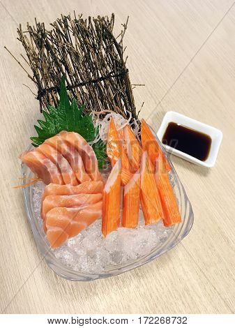 Salmon sushi japanese raw fish sashimi set served with crab stick (Kanikama) on ice dish with shoyu sauce on the table