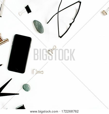 White office desk with supplies. mobile phone glasses scissors and office supplies on white background. Flat lay top view office table desk.