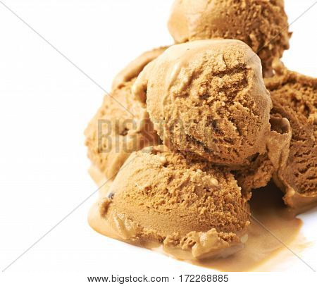 Pile of multiple melting caramel ice-cream ball scoops isolated over the white background, close-up crop composition with shallow depth of field