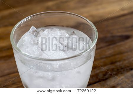 Close Up Glass Of Fresh Mineral Water With Ice Cubes On Wood Table With Vintage Color. Empty Ready F