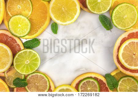 A vibrant frame made up of juicy citrus fruits, on a white marble texture, with copy space. Grapefruit, lime, lemon, and orange slices with mint leaves