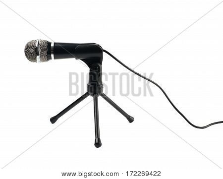Black microphone on a short rack stand, composition isolated over the white background
