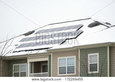 solar panel on the roof covered by snow after blizzard in winter