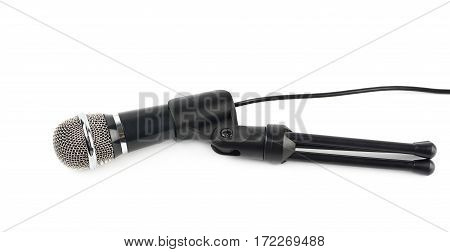 Black microphone on a short rack stand, lying on its side, composition isolated over the white background