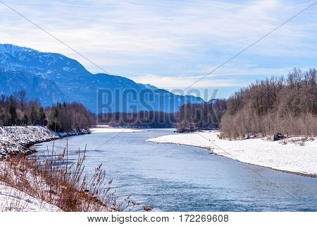 Majestic mountain river in winter over snow mountains and blue sky in Vancouver, Canada.