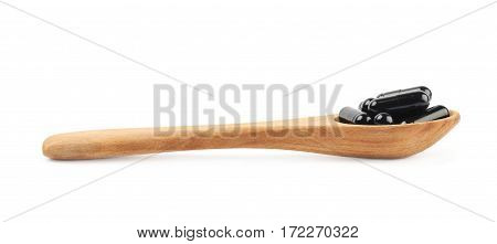 Spoon full of softgel black capsule pills isolated over the white background