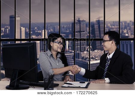 Business people handshake over the deal while sitting in the office with landscape background on the window