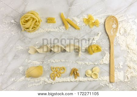 Various types of pasta on a white marble table with flour and a wooden ladle, shot from above