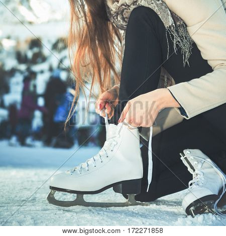 Closeup woman tie shoelaces at figure skates at ice rink close-up, ice skating