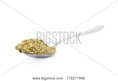 Spoon of green italian pesto isolated over the white background
