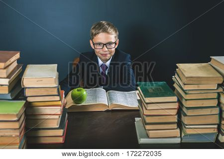 Cunning school boy sitting at the table with many books and one green apple. Smiling child dressed in school uniform and glasses. Blackboard. Student. Concept of education. Looking at camera