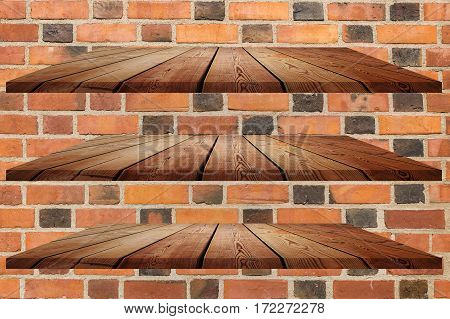 collection of wooden shelves on an red brick wall texture background.