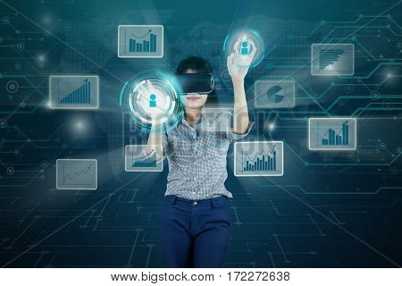 Female entrepreneur wearing virtual reality glasses while touching button screen with financial growth on the virtual screen