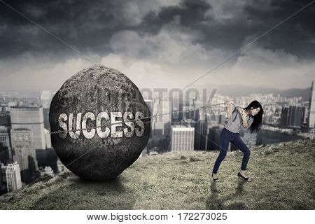 Beautiful businesswoman dragging a big stone with success word while walking on the hill
