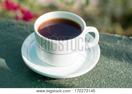 Morning cup of tea drinking on balcony on flower background
