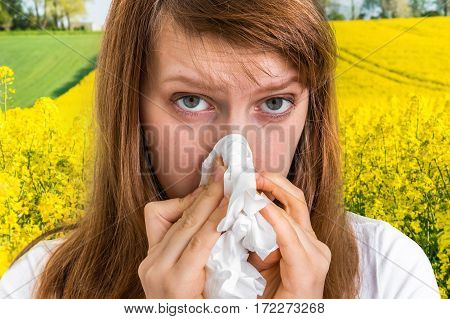Woman With Allergy On Yellow Rape Field Sneezing In Tissue