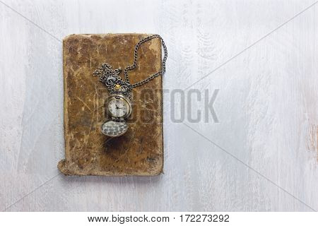 A photo of an old book, shot from above with a vintage chain watch, with a place for text