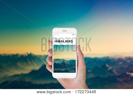 woman using her smartphone for searching the travel information of beautiful Himalayan landscape at the sunrise time Ladakh India. Traveling concept Himalayan range blurry background.