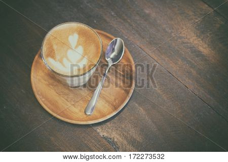 A Cup Of Piccolo Latte With Spoon And Wooden Saucer On Wooden Table